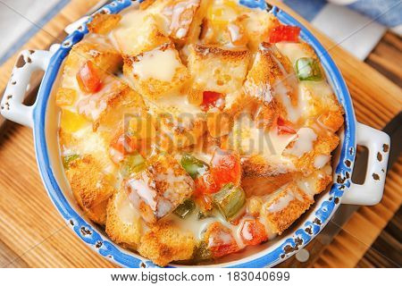 Freshly baked bread pudding in casserole dish on wooden board