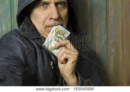 Man wearing hood holding a banknote in doubt closeup cropped portrait