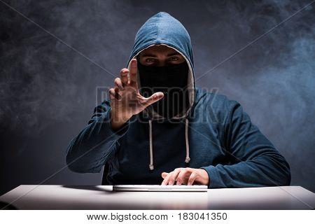 Computer hacker working in dark room