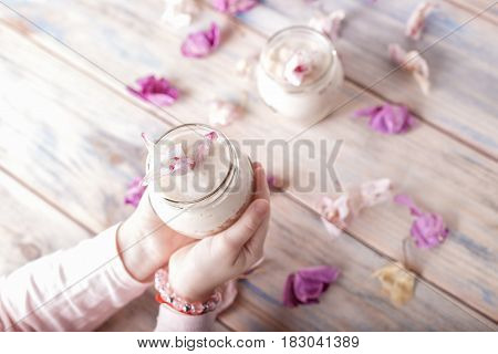 Baby holding yogurt in a jar. Healthy breakfast from yoghurt with muesli. dessert,