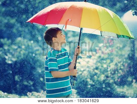 Child on rainy weather. Boy holding colourful umbrella under rain in summer