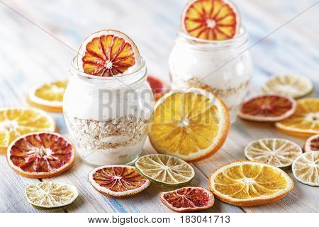 Delicious yoghurt with baked muesli and orange in a glass jar