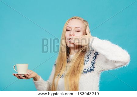 Addiction and caffeine need concept. Sleepy yawning blonde woman holding cup of coffee about to drink it.