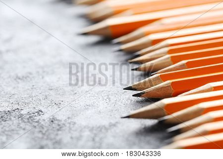 Yellow pencils on grey wooden table, close up