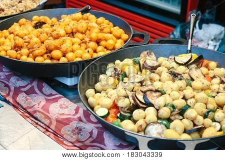 Of grilled vegetables. Vegetarian food. The outdoors and cooking on the fire. The street food. Prepared food on the market and special trading food stalls. The sale and purchase of food.