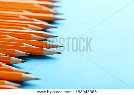 Yellow pencils on a blue background, close up