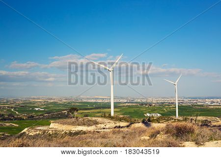Wind turbines generating electricity with blue sky - energy conservation concept.