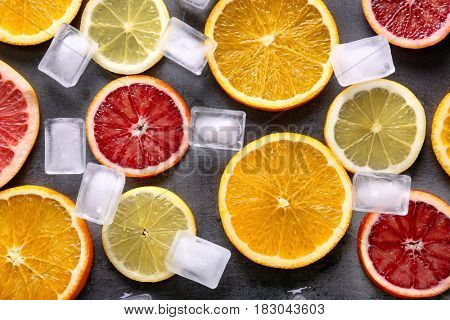 Juicy composition of citrus fruits and ice cubes on grunge background
