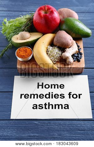 Healthy products and paper with text HOME REMEDIES FOR ASTHMA on wooden background