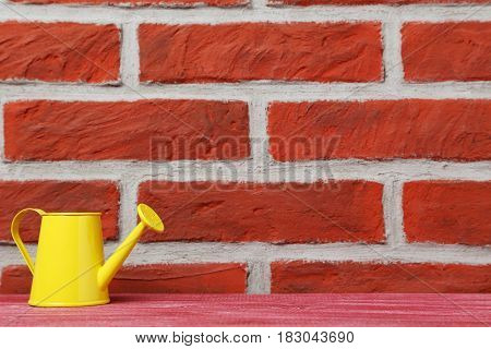 Yellow watering can on the brick wall background