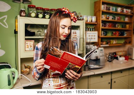Young Woman In Plaid Shirt And Apron Cooks In The Kitchen