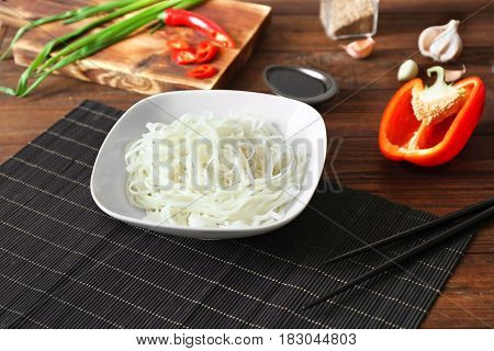 Plate with rice noodles on wooden table