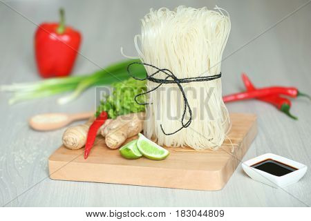 Wooden board with rice noodles on table