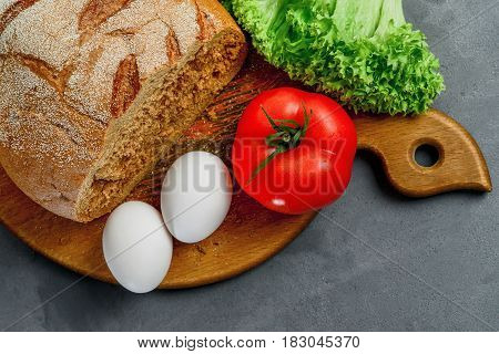 Eggs tomato lettuce leaves bread. Wooden board with Ingredients for cooking. From above.