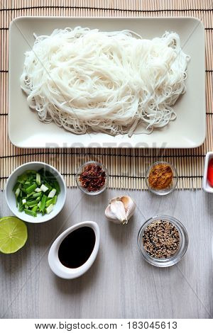 Plate with rice noodles and ingredients on wooden table