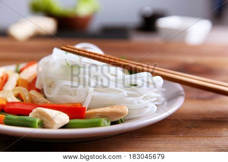 Plate with tasty rice noodle and vegetables on wooden table against blurred background