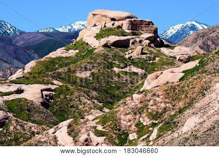Sandstone rock formations uplifted by the San Andreas Fault surrounded by green grasslands during spring taken in Cajon, CA