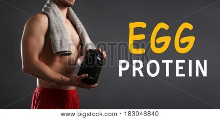 Egg protein concept. Muscular man with jar of food supplement on dark background