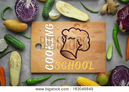 Cooking school concept. Wooden cutting board and fresh vegetables on gray background