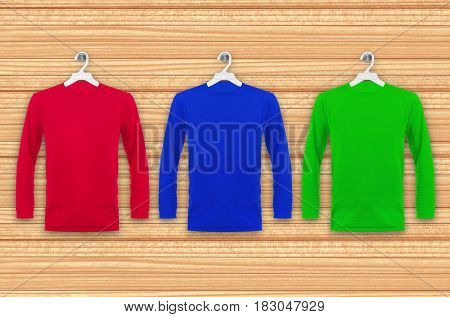 Colored T-shirts with long sleeves hanging on a wooden wall