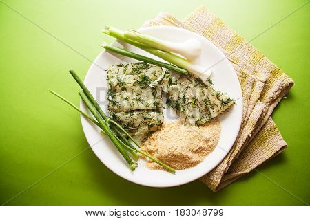 marinated cod willet with dill on green background