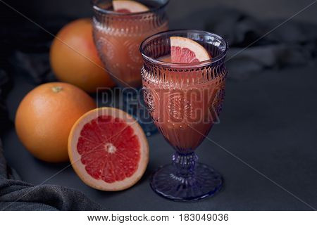 Glass of freshly squeezed grapefruit juice with fresh citrus fruits on dark background. Space for text.