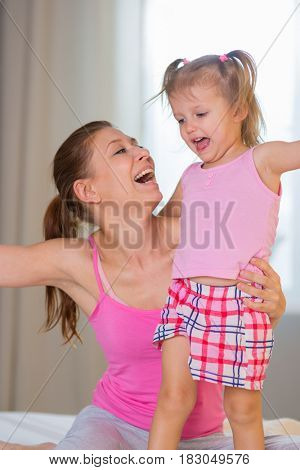 Mom and daughter in the bedroom on the bed having fun and embracing