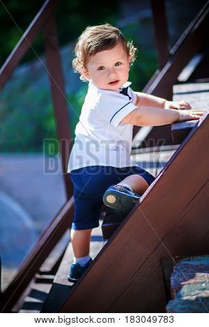 Little handsome boy climbs on the wooden stairs to the top. Todder in white shirt clings to step hands. The boy with curly hair looking at with interest.