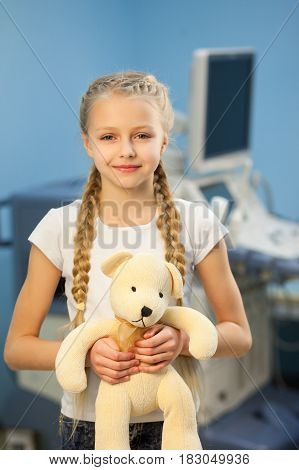 The girl with a soft toy in the hospital on a background of ultrasound machines smiling and playing