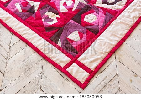 Part of color patchwork quilt with purple flowers pattern as background. Pink Scrappy blanket. Hobby, handmade, art Concept.