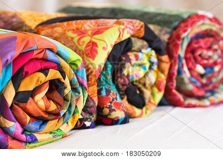 Three colored patchwork quilts twisted into close up. Colorful scrappy blankets folded as background. Handmade, hobby, art concept.