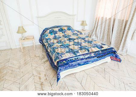 large double bed with a white and blue patchwork quilt in the white interior. scrappy blanket on the bed closeup. Dream, sleeping, art, hobby concept.