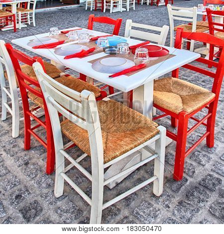 Alfresco restaurant with white and red table and chairs on the street, Crete, Greece. Square image