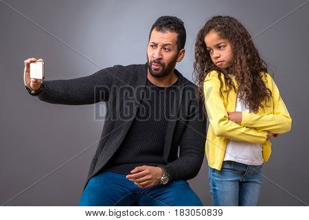 A black father taking selfie with a smartphone while his young daughter annoyed and standing with her arms crossed