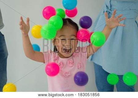 Happy children playing with their parents having fun with colorful balls.