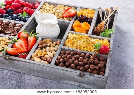 Old gray wooden box with variety of cold quick breakfast cereals and berries for breakfast, healthy eating concept, selective focus.