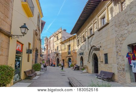 Barcelona, Spain - Nov 2nd, 2013:   Touring Europe - people visit small town of Barceloneta, on interior of Barcelona.  City in a city.  Charming cafes, shops, cobblestone street.