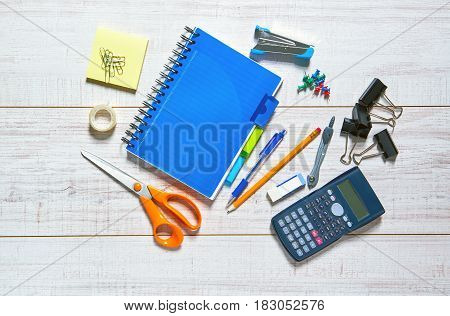 View of a wooden table with a notebook, pen, pencil, rubber, scissors, sellotape, calipers, stapler, clips pins and a calculator