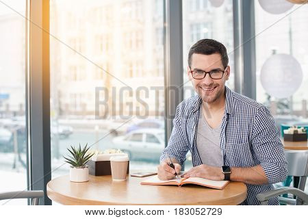 Coffee time. Handsome young man in cafe with big window. Man with cup of coffee to go. Man with glasses looking at camera and smiling