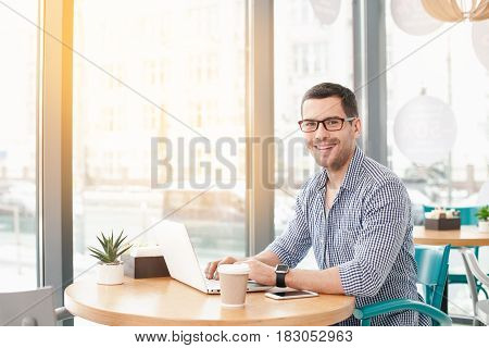 Coffee time. Handsome young man in cafe with big window. Man with cup of coffee to go. Man with glasses working with laptop, looking at camera and smiling