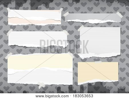 Ripped white and yellow notebook, copybook, note paper strips stuck with sticky tape on grey pattern created of heart shapes.