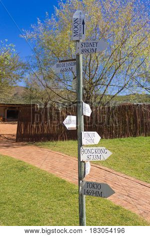 Funny distance signage pole from Oudtshoorn South africa. Arrows with distance indication