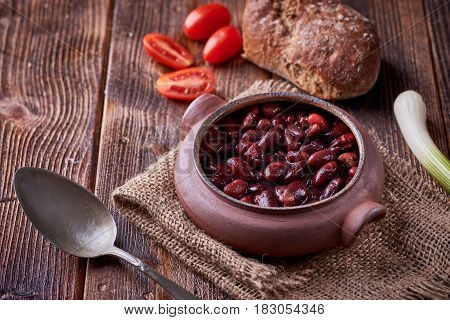 Bean soup in home crafted bowl with tomatoes on wooden table.