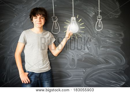 Teenager boy getting an idea with row of light bulbs - back to school education concept
