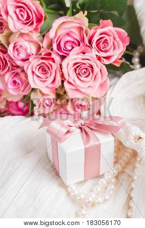 Female dress and jewellery with freah roses bouquet and present box with bow close up