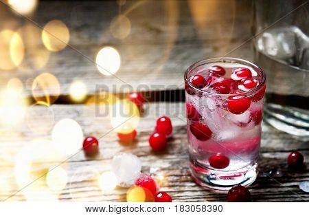 A Bottle and Shot of Vodka with Raspberry on old wooden background with gold bokeh