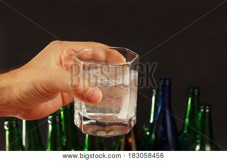 Hand with a glass of water and effervescent tablet of a hangover on a dark background.