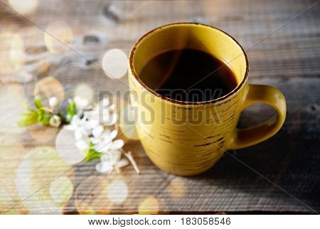 Coffee cup and flowers on garden table with dold bokeh.