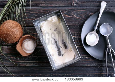 Metal tub with fresh ice cream for scooping and filling desserts on wooden background