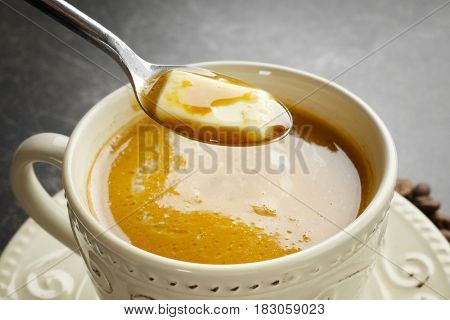Cup of tasty butter coffee and spoon, closeup